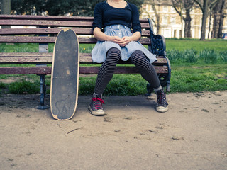 Woman with skateboard sitting on park bench