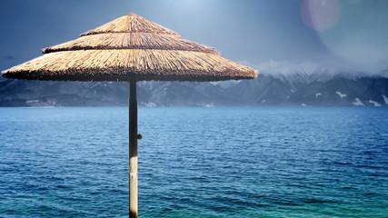 Beach umbrella on blue water seaside with snow peaks background