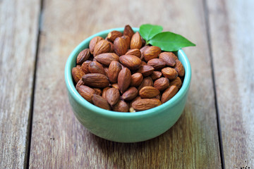 almonds a ceramic bowl on grained wood background