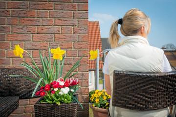 Frau sitzt auf dem Balkon im März