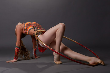 Graceful artistic gymnast performs with hoop