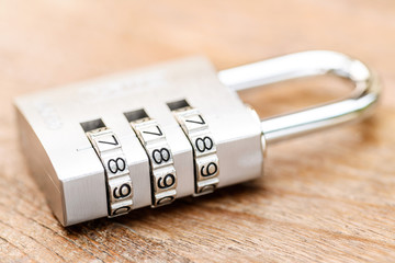 Combination padlock close up with chrome numbers on wooden backg