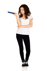 Woman pointing aside with big pencil.