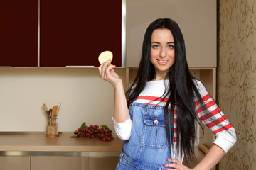 Brunette housewife in blue overalls holding a piece of apple and