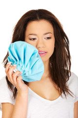 Woman with toothache and ice bag.