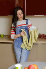 Housewife brunette in home clothes wipes saucer.