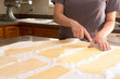 Chef trimming rolled pasta dough in a kitchen