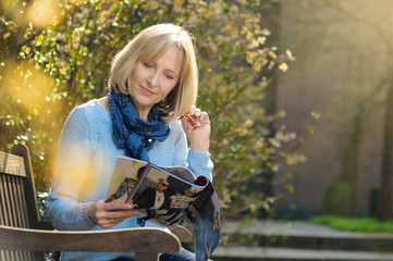 mature woman is reading a magazine in the garden