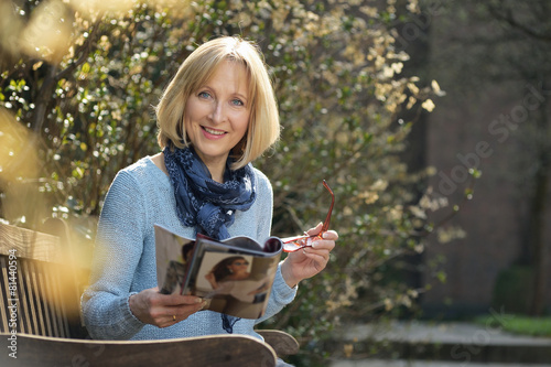 Leinwanddruck Bild smiling mature woman is reading a magazine
