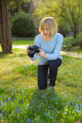 attractive mature woman is taking pictures in a park