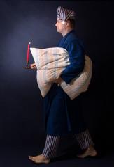 man in pajamas carries pillow