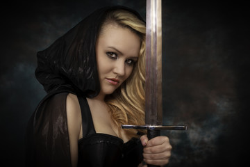Blonde Frau in schwarz mit Schwert