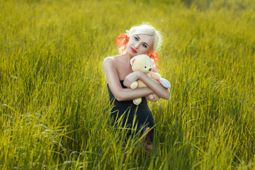 The girl and toy bear in a meadow.
