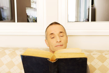 Mature man reading a book at home
