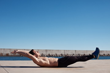 Handsome young athlete doing exercise for abdominal outdoors