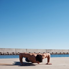 Strong and muscular athlete with naked torso doing push-ups outd