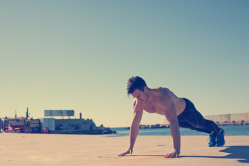 Young athlete doing push-ups outdoors (intentional vintage color
