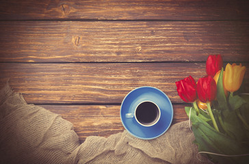 Cup of coffee with tulips near fabric