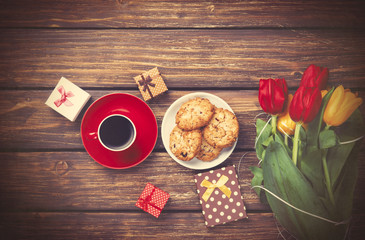 Cup of coffee with cookies and gifts