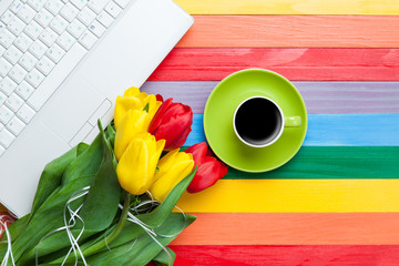 Cup of coffee with tulips and notebook