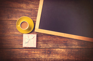 Cup of coffee near gift and blackboard