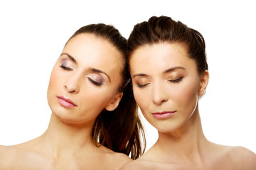 Two sisters with make up and eyes closed.