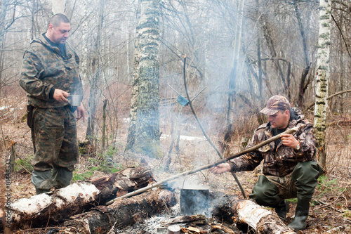 two hunters over the campfire - 81448333