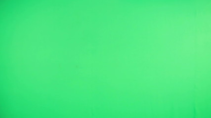 Woman hand using remote control on green screen background