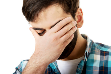 Young depressed man touching his face.