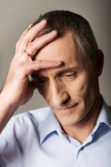 Depressed mature man touching his head