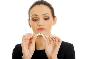 Businesswoman breaking cigarette.