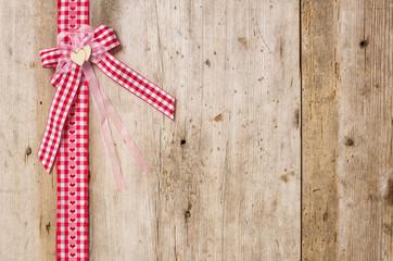 Rote Geschenkbänder mit Schleife vor rustikalen Holzbrettern
