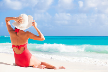 back view of woman in red swim suit and straw hat sitting on