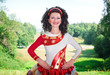 Young woman in red and white irish dance dress and wig posing