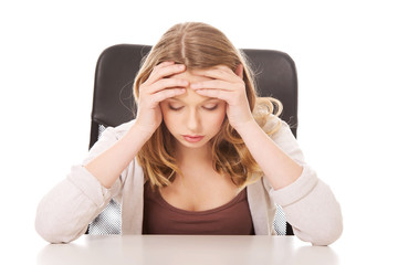 Young worried woman sitting at the desk