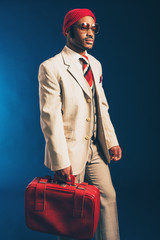 Fashionable Afro Guy Carrying his Red Suitcase