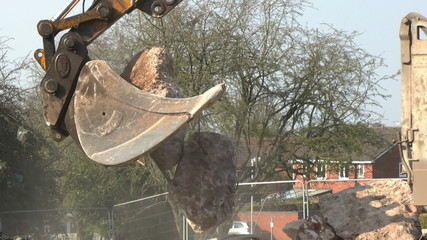 A mechanical digger moves rubble at a construction site