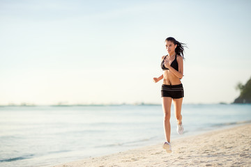 Sporty woman jogging on seaside