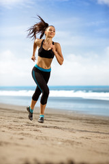 sport woman running in sea coast on sunny day