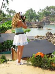Girl with a camera on Palolem beach. South Goa, India