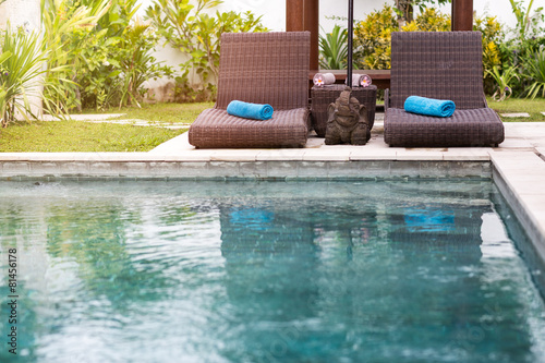 Clear blue water in swimming pool and sunbeds