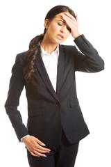 Full length businesswoman having huge headache