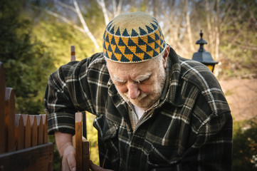 old man repairing a gate