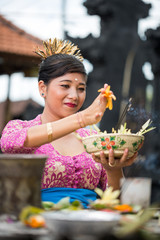 Balinese woman in temple with offering for Gods