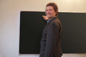 Male teacher writes on blackboard with a chalk
