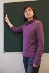 Woman writing with chalk on blackboard at classroom