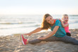 Healthy mother and baby girl stretching on beach in the evening - 81457963