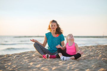 Healthy mother and baby girl doing yoga on beach in the evening