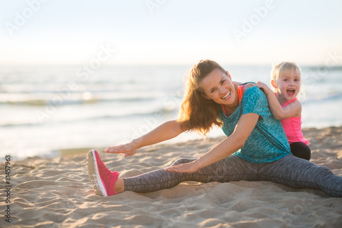 Zdrowy matki i dziewczynki rozciąganie na plaży w wieczór