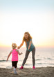 Mother and baby girl having fun time on beach in the evening